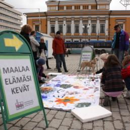 Ihmisiä Turun kauppatorilla tekemässä maalausta sekä kyltti