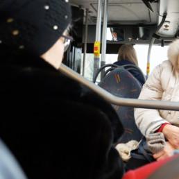 Iloinen seniorimatkustaja bussissa