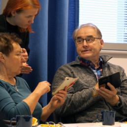 Kolme ihmistä tutkimassa kännykästä asioita