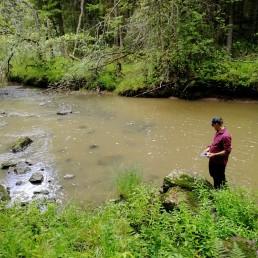Janne Tolonen asettamassa lämpötilamittaria leveän puron rannalla.