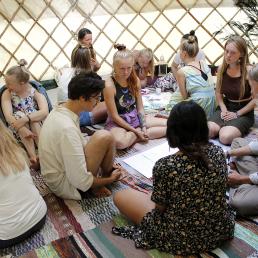 Ihmisiä ryhmittäin lattialla juttelemassa ja piirtämässä unelmatyöpajan visiota