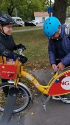 Fysioterapeutti ohjaamassa senioria kaupunkipyörän satulan säätämisessä.