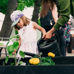 lapsi kastelee kukkia